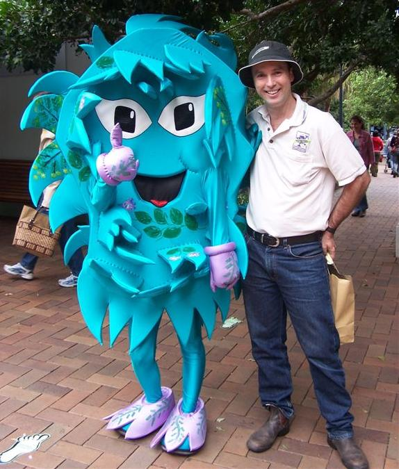 Greg Brown is helped by Weedie the Weed at a community event